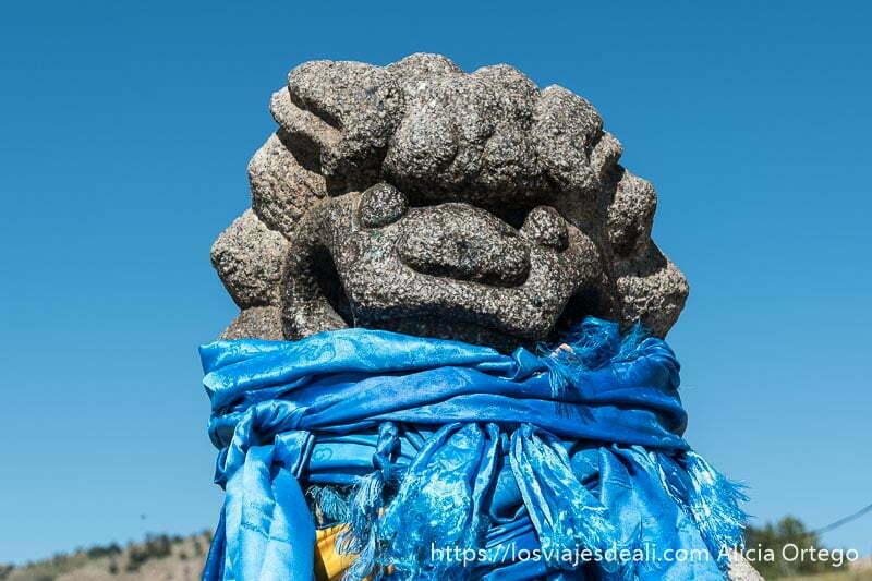 león de piedra con muchos pañuelos de seda azul anudados alrededor del cuello en mongolia central