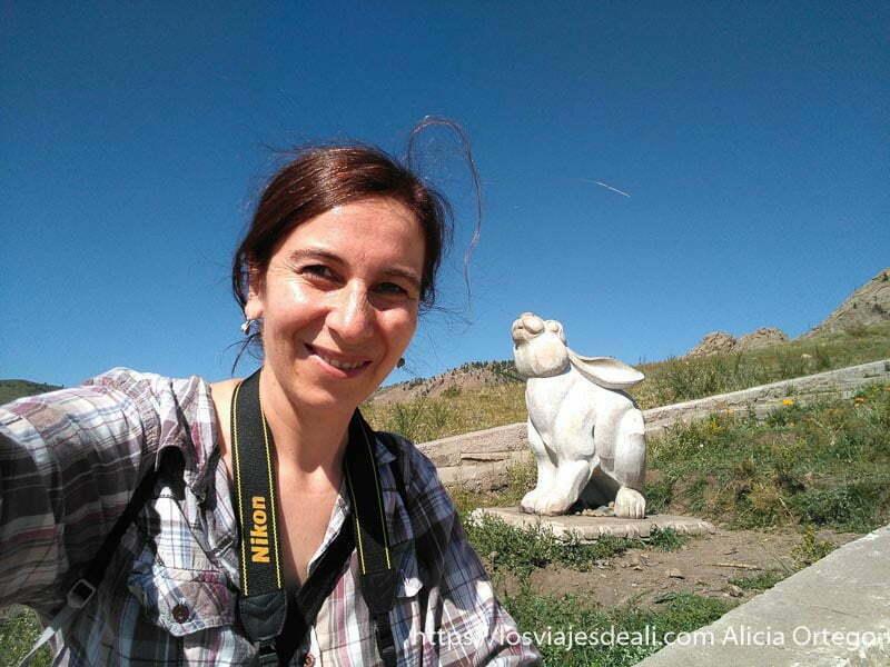 selfie con una estatua de conejo detrás