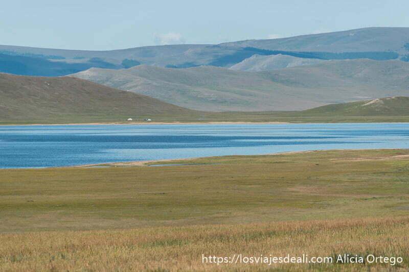lago de colores muy azules con montañas detrás y prado de hierba delante en Mongolia Central