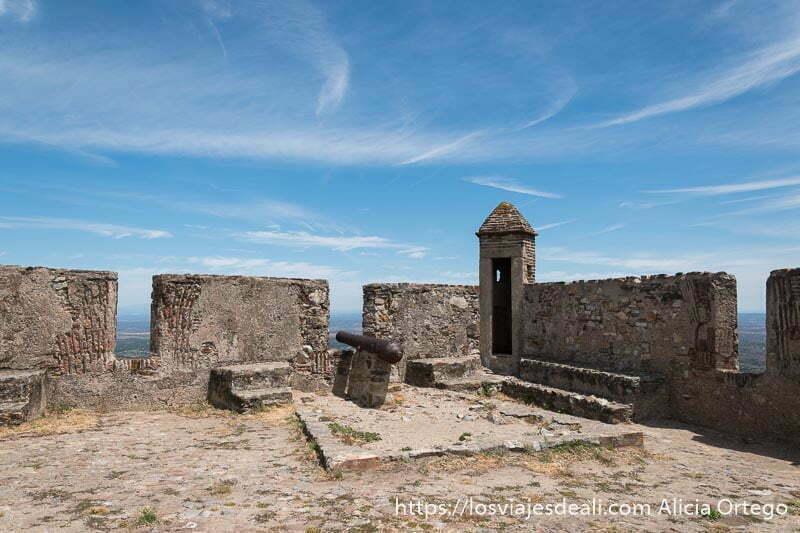 esquina de parte superior de murallas con almenas y un cañón de hierro antiguo