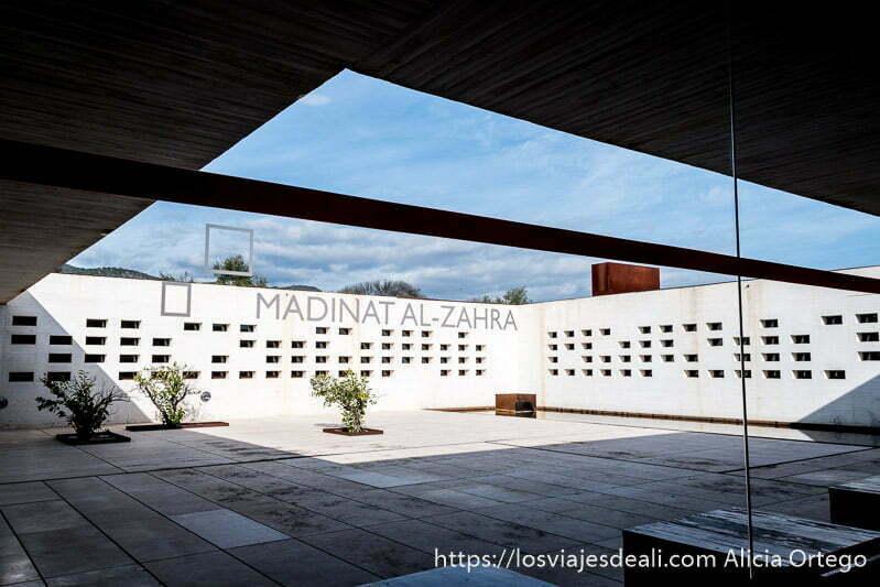 patio del museo de madinat al-zahra con paredes blancas y tres arbustos