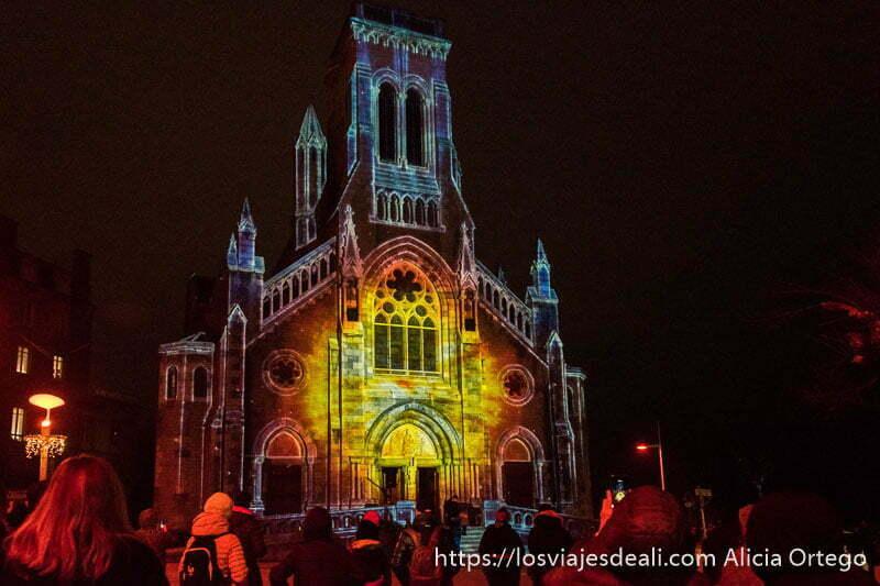 fachada de la iglesia de san eugene iluminada por navidad con gente delante mirando el espectáculo en la excursión a san juan de luz y biarritz