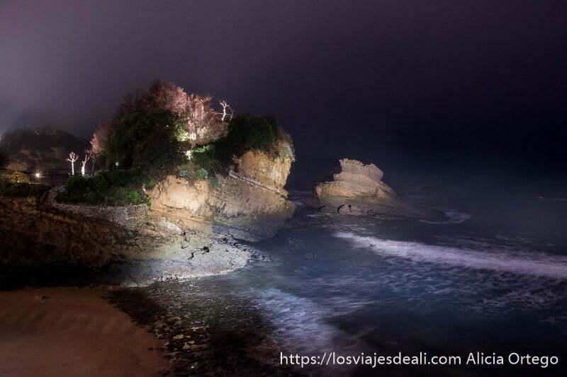 foto noctura de playa con grandes rocas con vegetación en parte superior y olas del mar iluminadas por la noche en la excursión a san juan de luz y biarritz