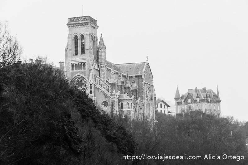 vista de la iglesia san eugene con torre cuadrada y al fondo otro edificio con tejados de pizarra negra en la excursión a san juan de luz y biarritz