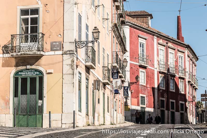 calle con raíles del tranvía y casas pintadas de colores en el centro de lisboa