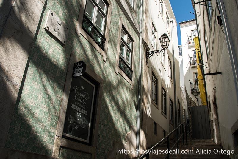 calle en cuesta con barandilla en el centro y fachada llena de azulejos en tonos verdes medio en sombras y sol en lisboa