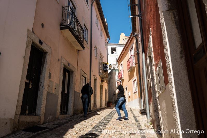 calle en cuesta empedrada con una chica que se ha dado la vuelta y sonríe a cámara y casas pintadas de colores en alfama