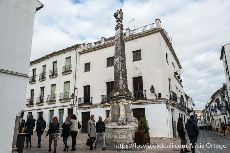 comienzo de la plaza del potro con estatua sobre columna de piedra entre casas blancas