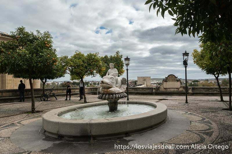 fuente con estatua de mármol de persona montada en animal mitológico y al fondo la torre de la calahorra en el centro histórico de córdoba