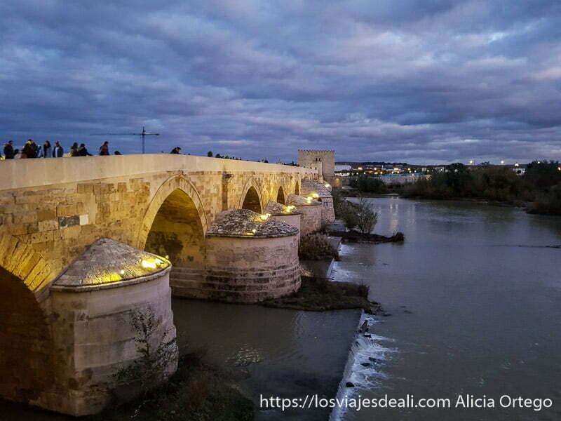 puente romano iluminado al anochecer con grandes nubes azules encima