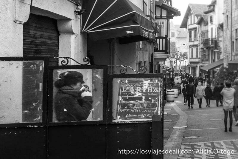 calle republique con gente andando y una chica con gorra y bufanda bebiendo una taza de café en la excursión a san juan de luz y biarritz
