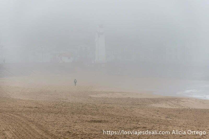 playa con mucha niebla y al fondo una figura andando y más allá una torre blanca