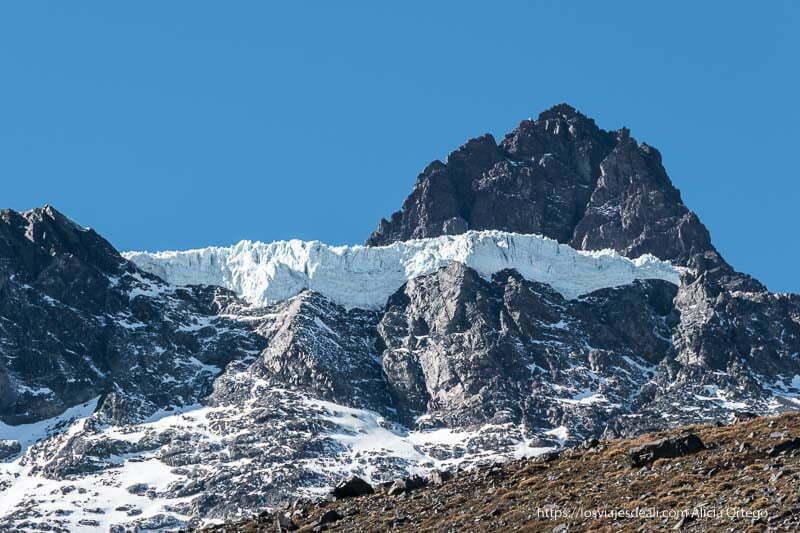 gran pared de roca con glaciar de hielo blanco y azul y cielo muy azul en la escapada al cajón del maipo