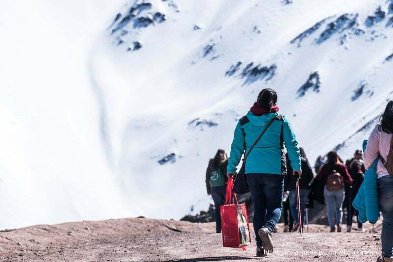 gente andando con bolsas de comida por pista de tierra y al fondo gran ladera nevada en el embalse de el yeso