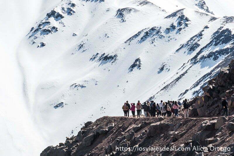 gente andando por la pista con ladera de nieve detrás en la escapada al cajón del maipo