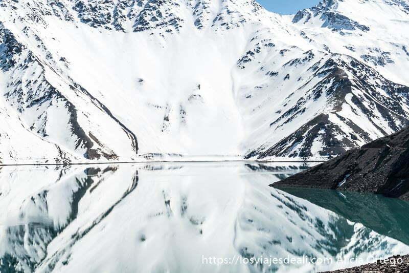 ladera de montaña muy nevada salpicada de rocas y reflejándose perfectamente en el agua con forma de prisma