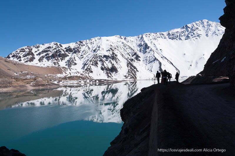 personas al borde del camino a contraluz como siluetas y detrás el embalse de el yeso y las montañas nevadas reflejándose en el agua con cielo muy azul