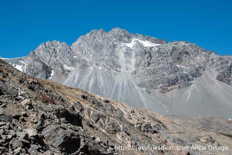 montaña de roca gris con un poquito de nieve en la cumbre y parte de la ladera convirtiéndose en grava en los alrededores del embalse de el yeso