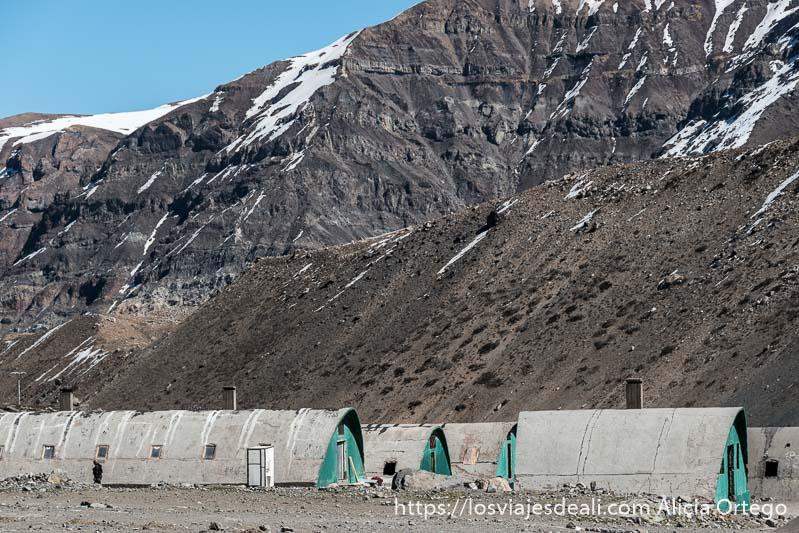 hangares del antiguo campamento de trabajadores con forma semicircular y puertas pintadas de verde y detrás montañas de roca con un poco de nieve en la escapada al cajón del maipo