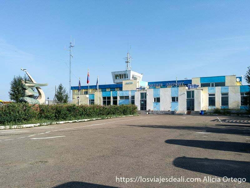 edificio de terminal de aeropuerto de Murun de una sola planta, antiguo y pintado de blanco y azul