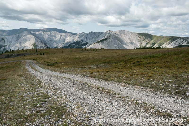 camino de piedras atravesando prado de hierba un poco seca y al fondo horizonte de montañas de roca gris y muchas nubes
