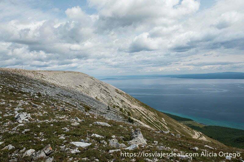 lago khovsgol a la derecha con diversos tonos azules y montaña a la izquierda con roca y hierba