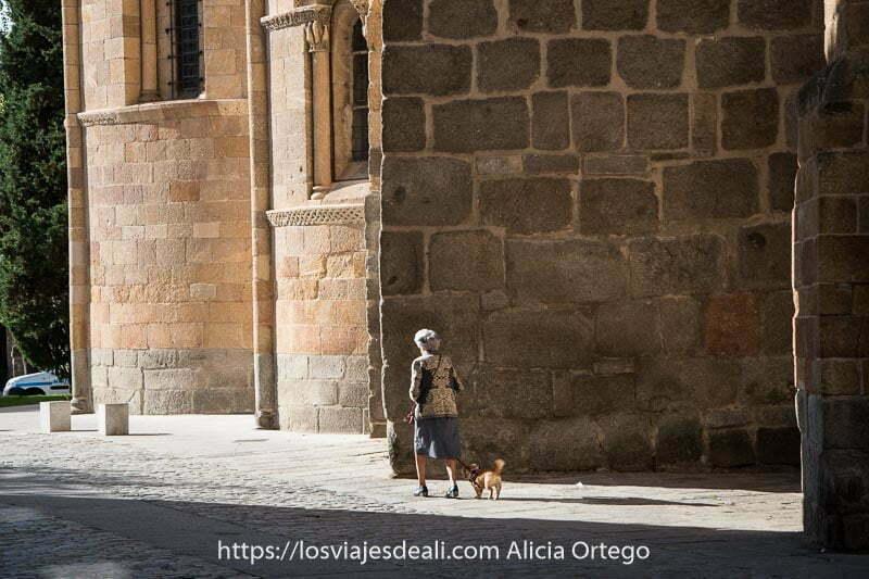 mujer mayor paseando a su perrito junto a una iglesia románica en el centro de ávila