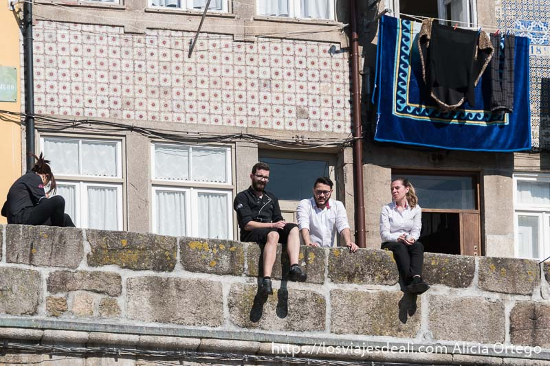 camareros de restaurantes de la ribeira descansando al sol sentados en un muro de piedra y detrás casa con azulejos en la fachada razones para viajar a oporto