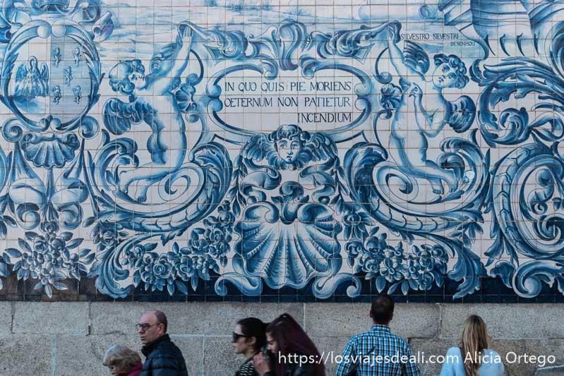 azulejos de colores azules donde se ve a unos ángeles y gente pasando delante de ellos razones para viajar a oporto