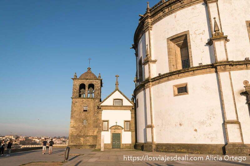 monasterio con edificio de forma circular y al lado pequeña iglesia con campanario al lado en piedra y paredes blancas en oporto