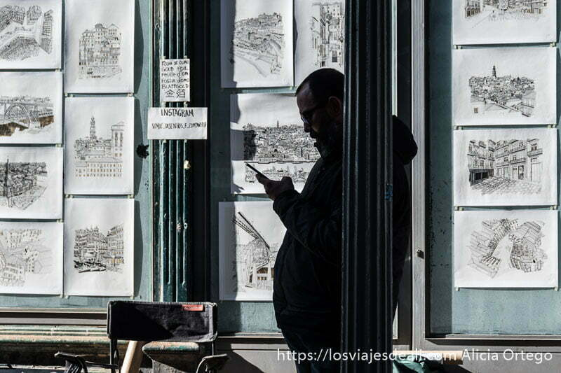 silueta de hombre con barriga apoyado de perfil en una farola de hierro mirando el móvil y detrás una pared llena de dibujos en blanco y negro de oporto