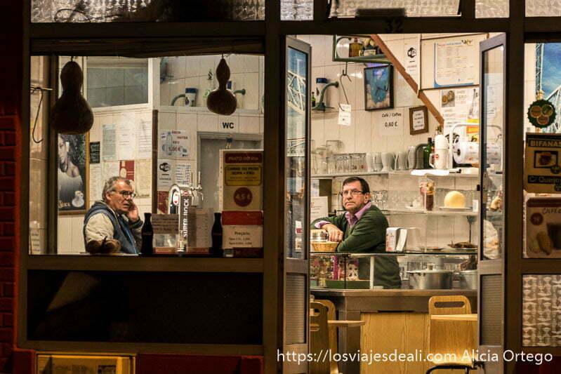 dos hombres dentro de un bar por la noche, uno hablando por el móvil y el otro mirando la tele en oporto