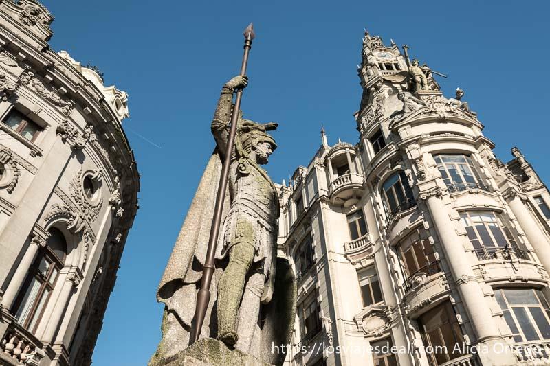 estatua de piedra de guerrero con casco apoyado en su lanza visto desde abajo y detrás edificios modernistas bajo cielo muy azul