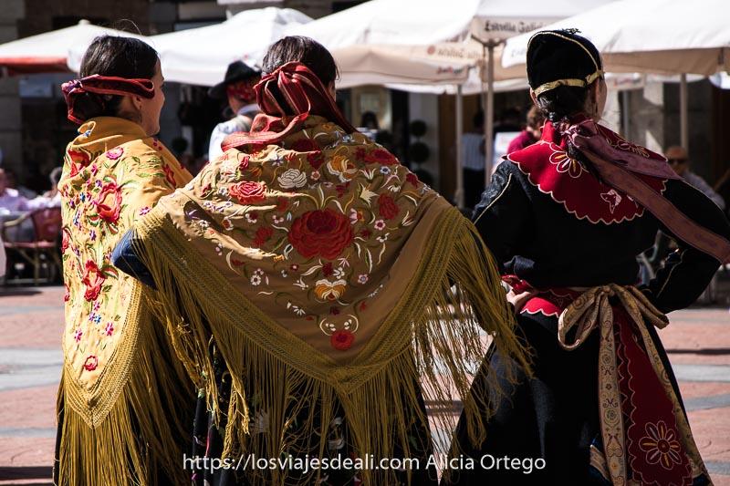 tres mujeres vestidas con trajes regionales de espaldas, con mantones bordados con flores