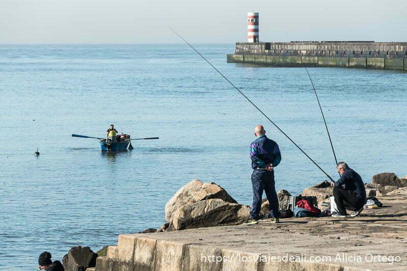 hombre con dos cañas de pesca en el muelle junto a la desembocadura del Duero y barca de pesca acercándose con los remos en alto