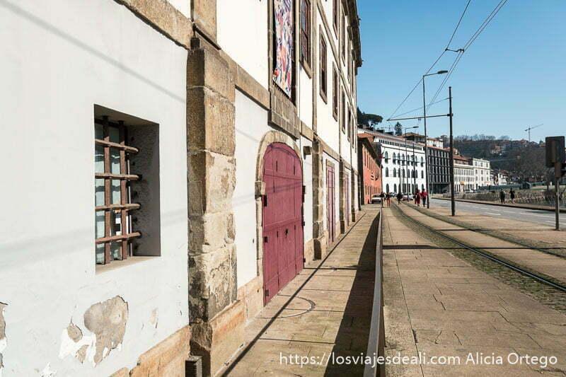 paseo junto al río Duero con gran edificio de piedra y encalado con puertas de madera pintadas de rojo cerradas