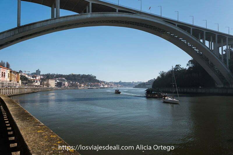 puente de la arrábida de oporto que es de hormigón con tres barcos navegando por el río debajo de él y camino en curva