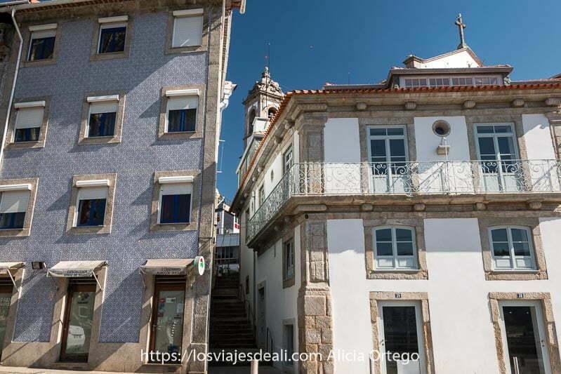 casas de forma irregular en el camino a foz do douro con campanario asomando por detrás de la más baja