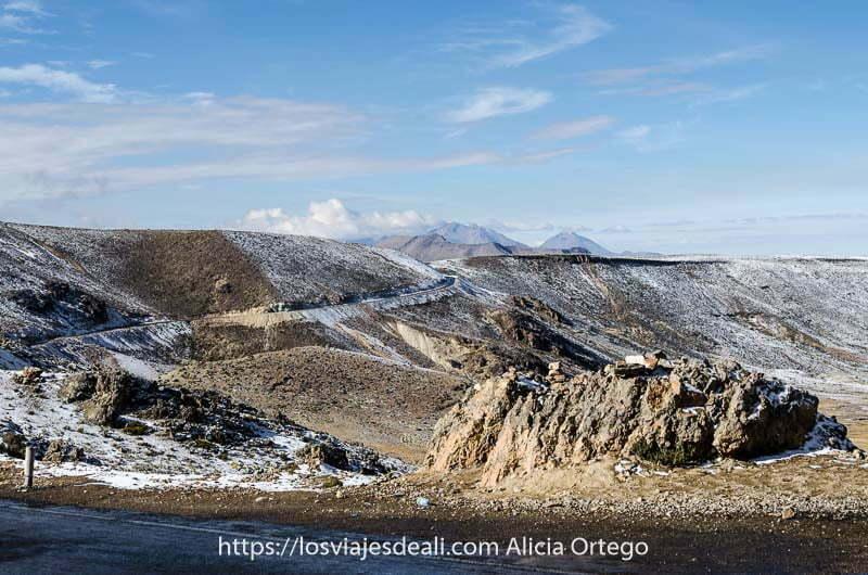 paisaje del altiplano con carretera con curvas y volcanes al fondo, con una ligera nevada recién caída, uno de los lugares maravillosos de Perú