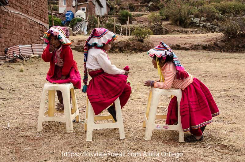 tres niñas pequeñas con gorros de lana de colorines y faldas rojas con vuelo en cuatro banquetas de plástico puestas en fila a orillas del lago titicaca uno de los lugares maravillosos de perú