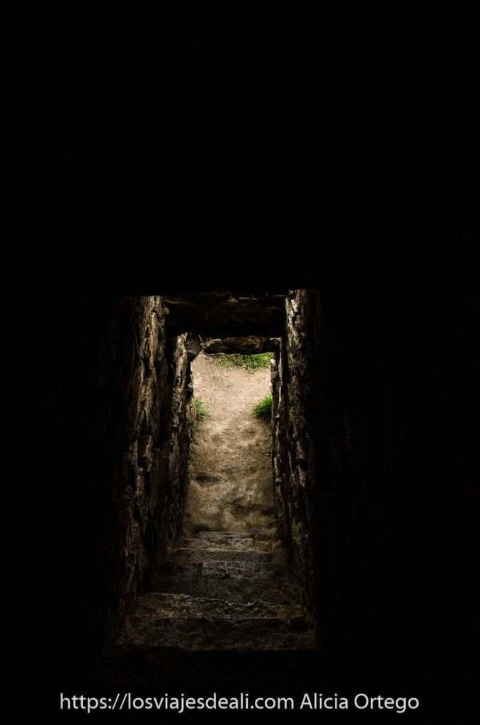 pasillo oscuro con escaleras de piedra que bajan hacia rectángulo de luz del exterior en chavín de huántar uno de los lugares maravillosos de perú