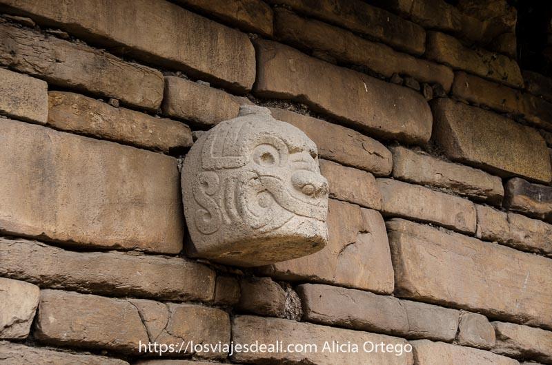 cabeza de piedra con forma de jaguar con ojos y colmillos grabados en una pared de piedra de chavín de huántar