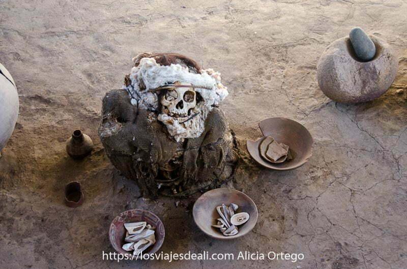 momia peruana con varios cuencos alrededor con conchas y trozos de cerámica en el cementerio de chauchilla