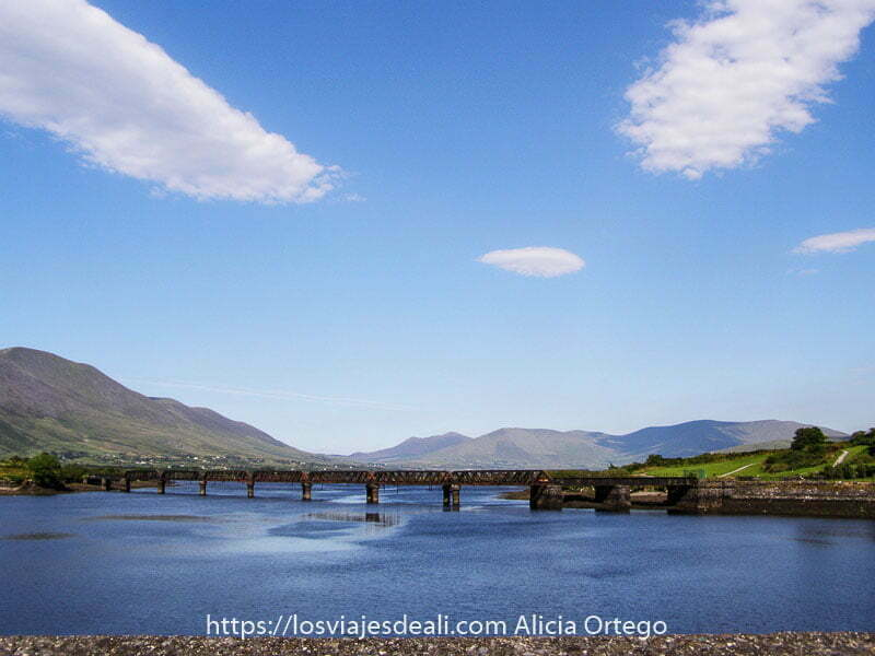 puente de hierro cruzando río ancho con montañas al fondo en Caherciveen en Ring of Kerry