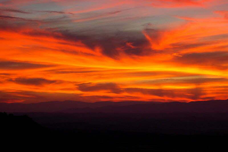 cielo lleno de nubes rojas y amarillas con horizonte de montañas en la Alcarria atardeceres del mundo