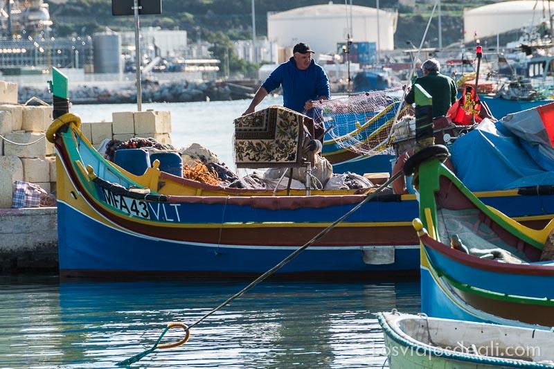 pescadores trajinando con redes en su barca de colores en el puerto de marksaxlokk