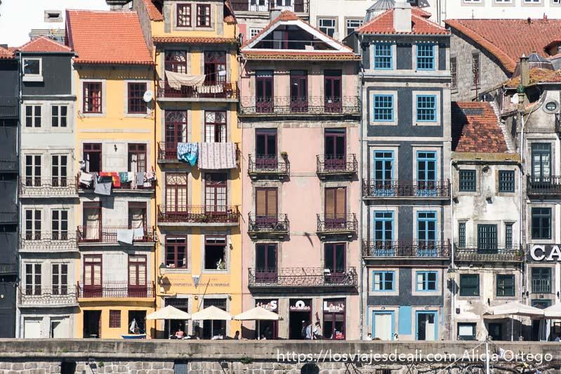 línea de fachadas estrechas y pintadas de colores con ropa tendida en la Ribeira uno de los lugares que ver en Oporto