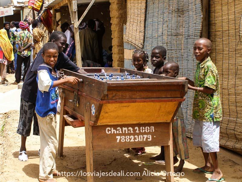 niños jugando al futbolin al aire libre en el mercado africano de gorom gorom