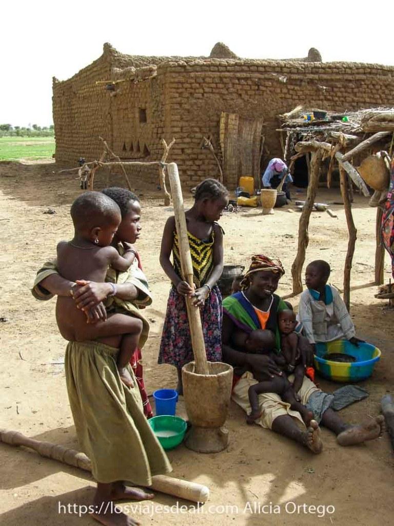 mujeres sentada en el suelo con dos bebés mellizos amamantándolos y una niña moliendo mijo a su lado con un gran palo