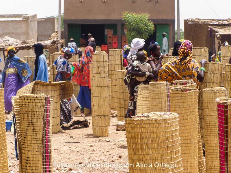 venta de esterillas grandes enrolladas y puestas de pie y mujeres entre ellas vestidas de colores comprando